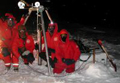 Scientists gathered around a robotic ice probe.